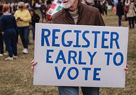 拿着提前登记投票标志横幅的人