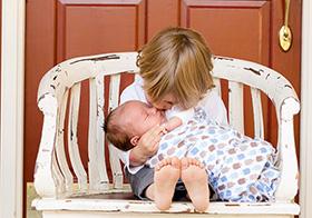 可爱的金发小朋友亲吻着婴儿