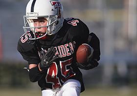 抱着橄榄球奔跑的男孩